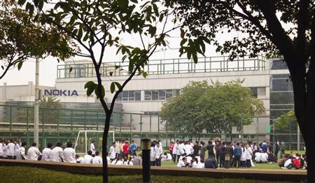 Nokia factory workers protest on a football pitch outside the factory in Dongguan, Guangdong province